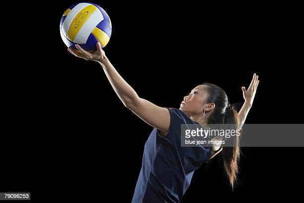 A female volleyball player preparing to serve.