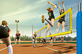 Female volleyball gameplay action in sunny day