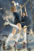Female volleyball player jumping for the ball on cloudy sky background
