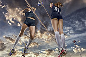 Female volleyball players jumping for the ball on cloudy sky background
