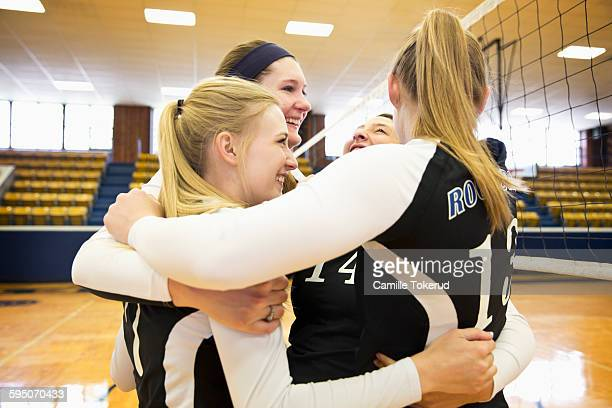 Female Volleyball teammates hugging