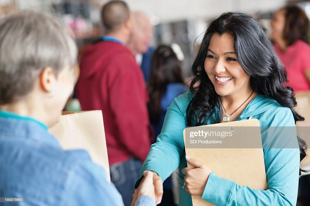 Female volunteer greeting woman at donation facility : Stock Photo