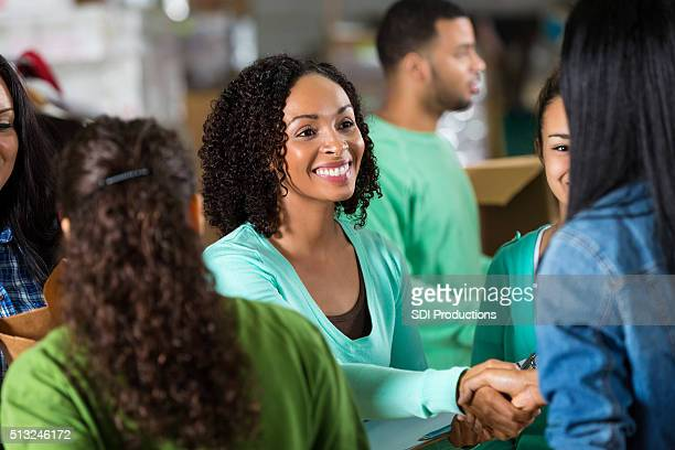 Mulher com voluntários cumprimenta mulher no Banco alimentar