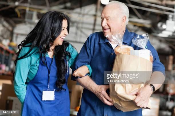 Female volunteer helping man walking out with groceries