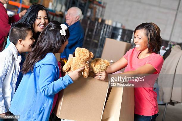 Female volunteer receiving toy donations from family