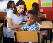 Female Volunteer teacher and elementary school boy smiling to camera