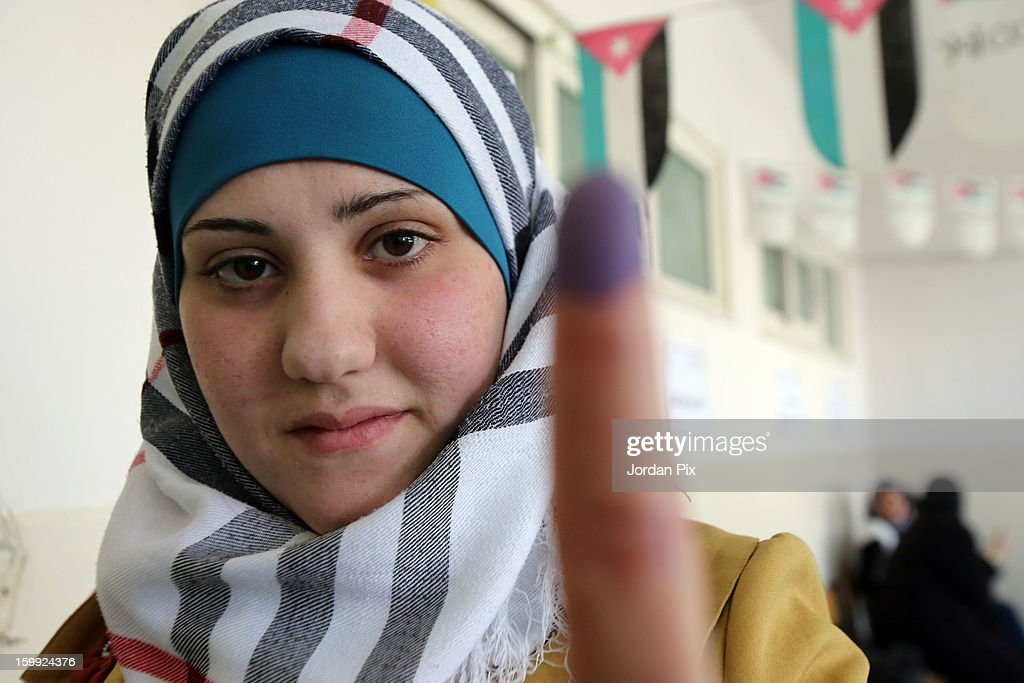 A female voter holds up her ink-stained finger as Jordanians vote in the parliamentary elections on January 23, 2013 in the city of Zarqa, Jordan. Jordan's election is being boycotted by the Muslim Brotherhood's political wing, the Islamic Action Front (IAF), who claim that the system is rigged favorably to supporters of the king, who for the first time will appoint the new prime minister.