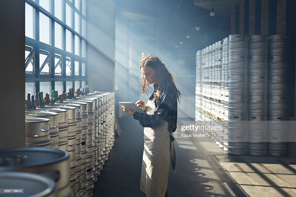 Female waiter counting beer keg's using tablet : Stock Photo