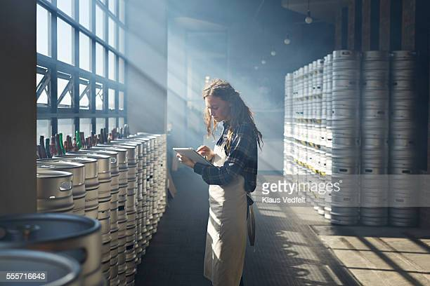 Female waiter counting beer keg's using tablet
