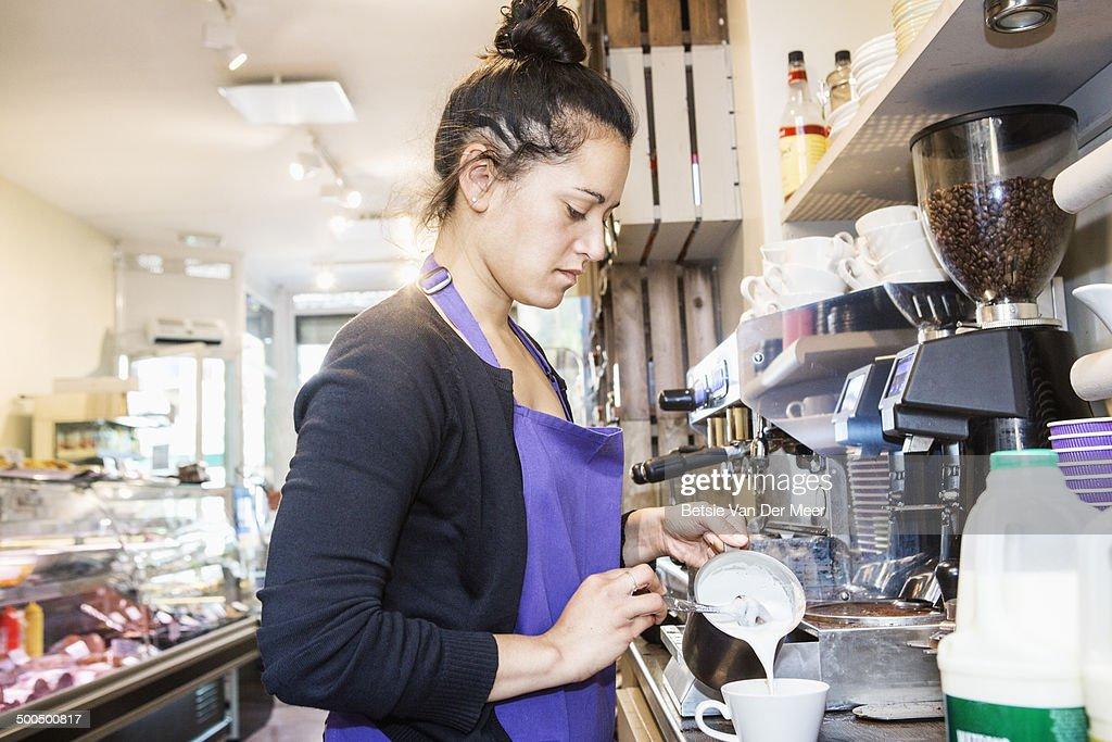 female waitress making coffee in delicatessen shop