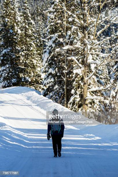 Female walking along snow covered road with snow covered trees