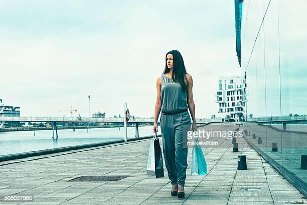Femme marchant avec des sacs en dehors