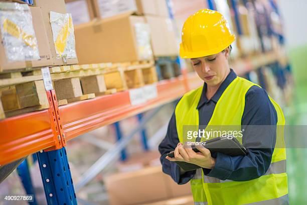Donna facendo una lista di controllo dei Dipendenti magazzino