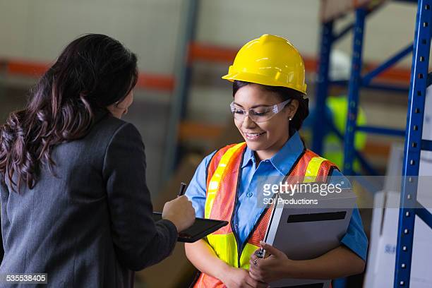 Female warehouse worker and supervisor checking shipping order