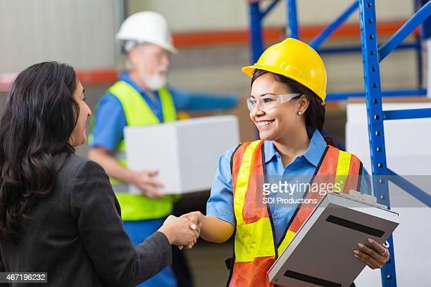 Weiblichen Lager Arbeiter Hände schütteln mit weibliche Mitarbeiter