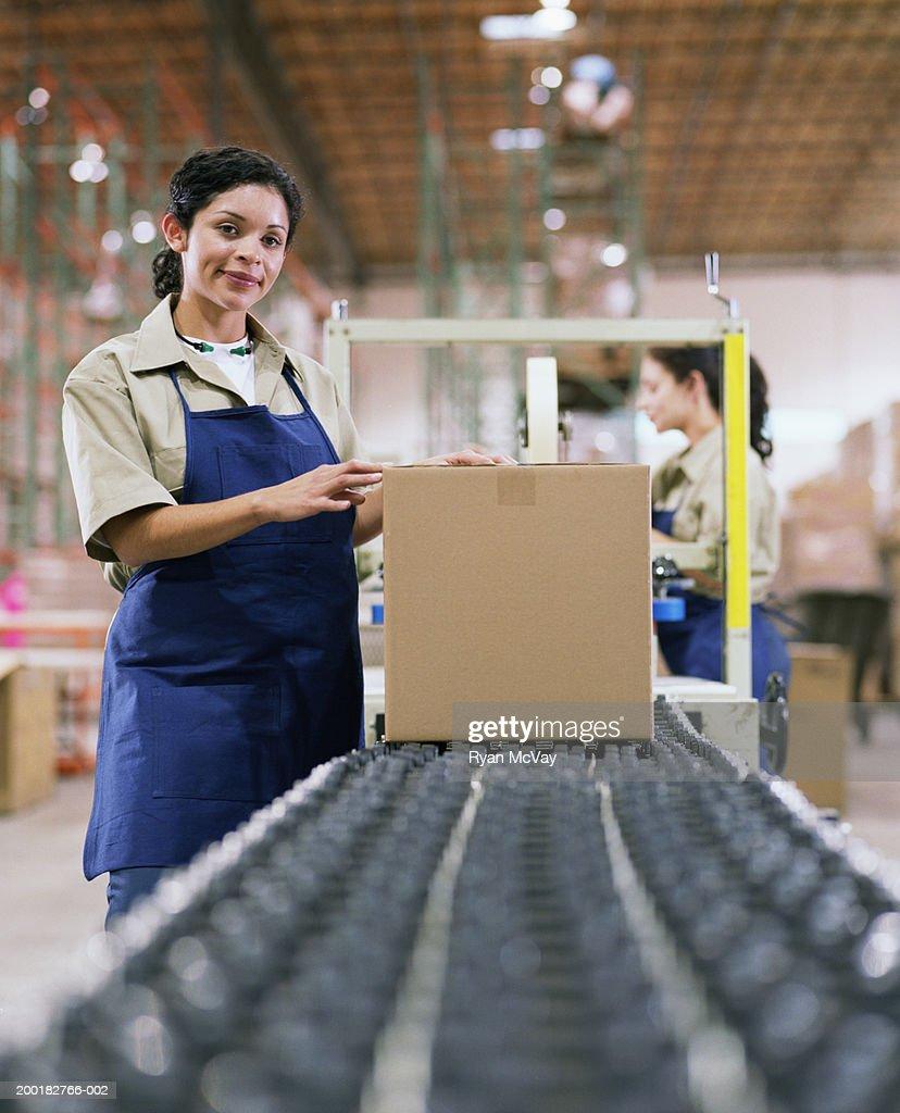 Female warehouse worker standing by conveyor belt : Stock Photo