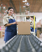 Female warehouse worker standing by conveyor belt