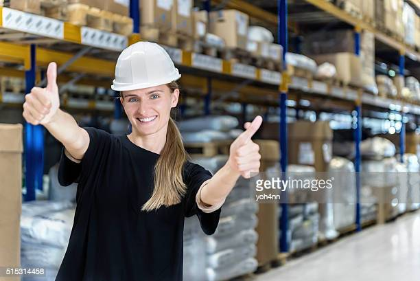 Female warehouse worker with thumbs up