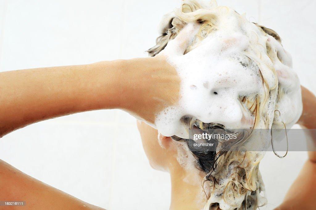 Female washing hair by shampoo.