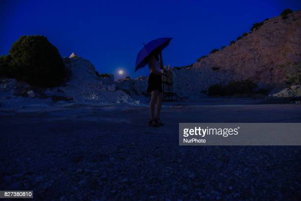 A female watching the fullmoon at the ancient theatre place of Aulida Greece on 8 August 2017 At the ancient theatre place of Aulida the place is...