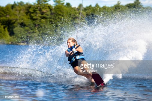 A female water skier rips a turn causing a huge water spray while skiing on Cobbosseecontee Lake near Monmouth, Maine. : Stock Photo