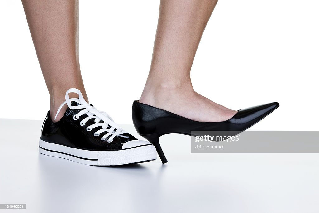 Female wearing a dress shoe and sneaker : Stock Photo