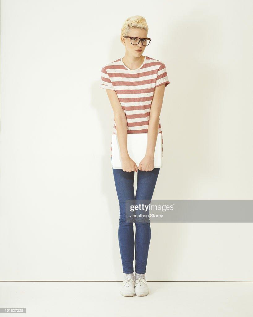 female wearing glasses holding laptop