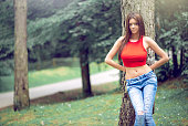 Young adult trendy woman posing braless in authentic natural mountain forest location. Wearing red top and jeans trousers. Toned image.