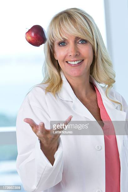 Female wearing lab coat tossing apple in air