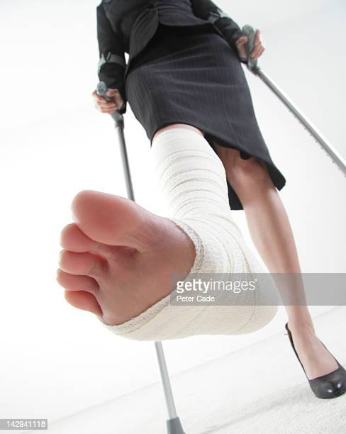 female wearing suit on crutches with bandages foot