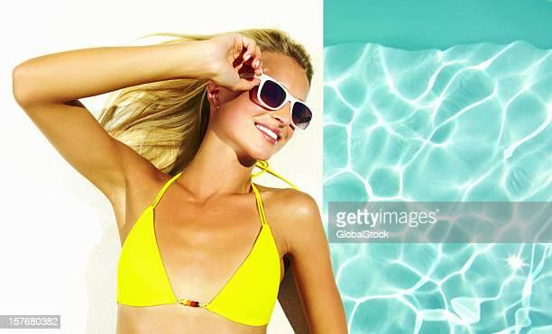 Weibliche trägt eine Sonnenbrille und bikini liegen am pool