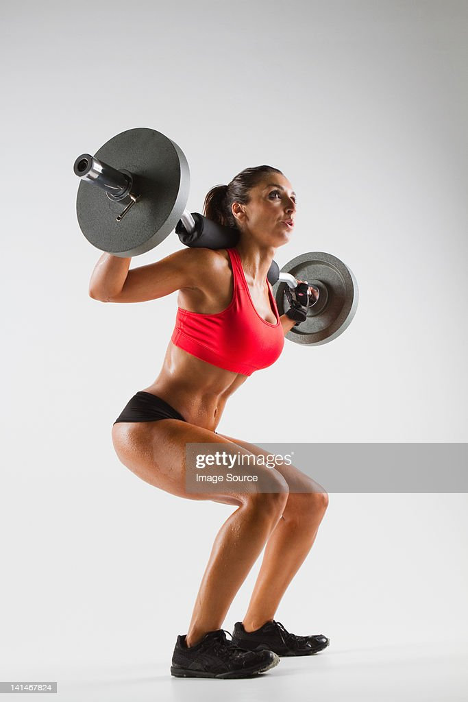 Female weightlifter using barbell : Stock Photo