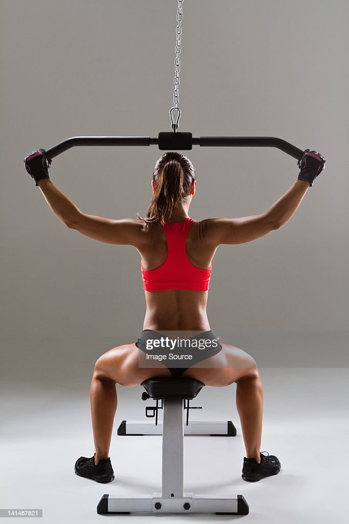 Female weightlifter using weight machine : Stock Photo