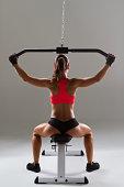 Female weightlifter using weight machine