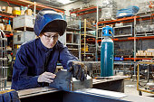 Young Female Welder Inspecting Her Work In Factory Wearing Protective Safety Gear