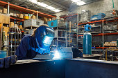 Young Female Welder Working In Factory Wearing Protective Safety Gear