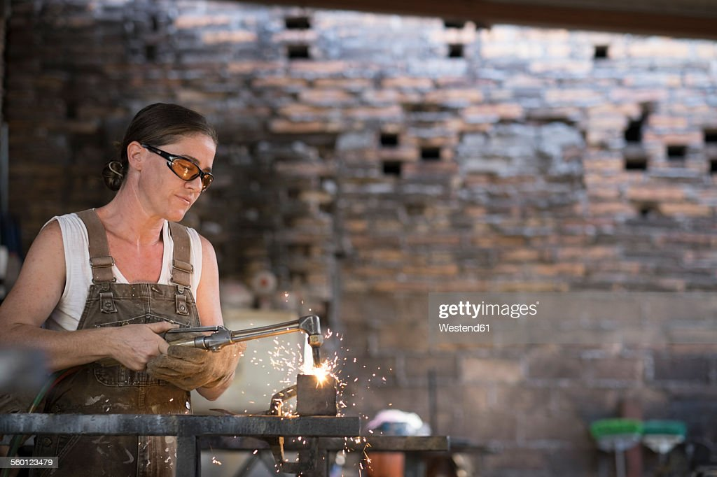Female welder working in metal workshop