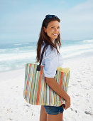 Female with a beach bag and smile at sea shore