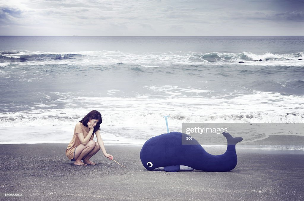 Female with a whale in the beach : Stock Photo