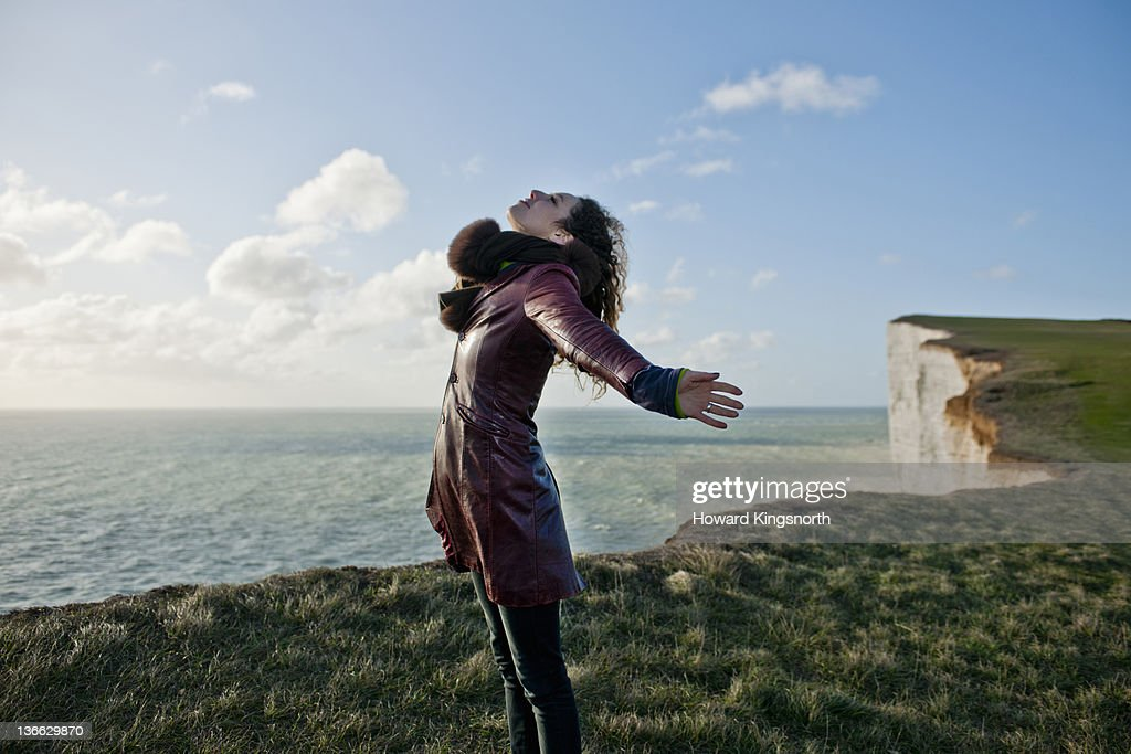 female with arms outstretched on windy clifftop : Stock Photo