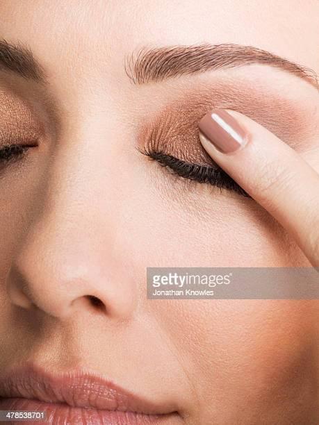 Female with closed eyes, finger on eyelid