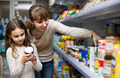 Smiling spanish  female with daughter choosing canned goods in food store
