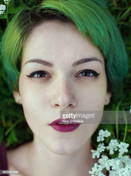 Female with green hair lays in grass with white flowers