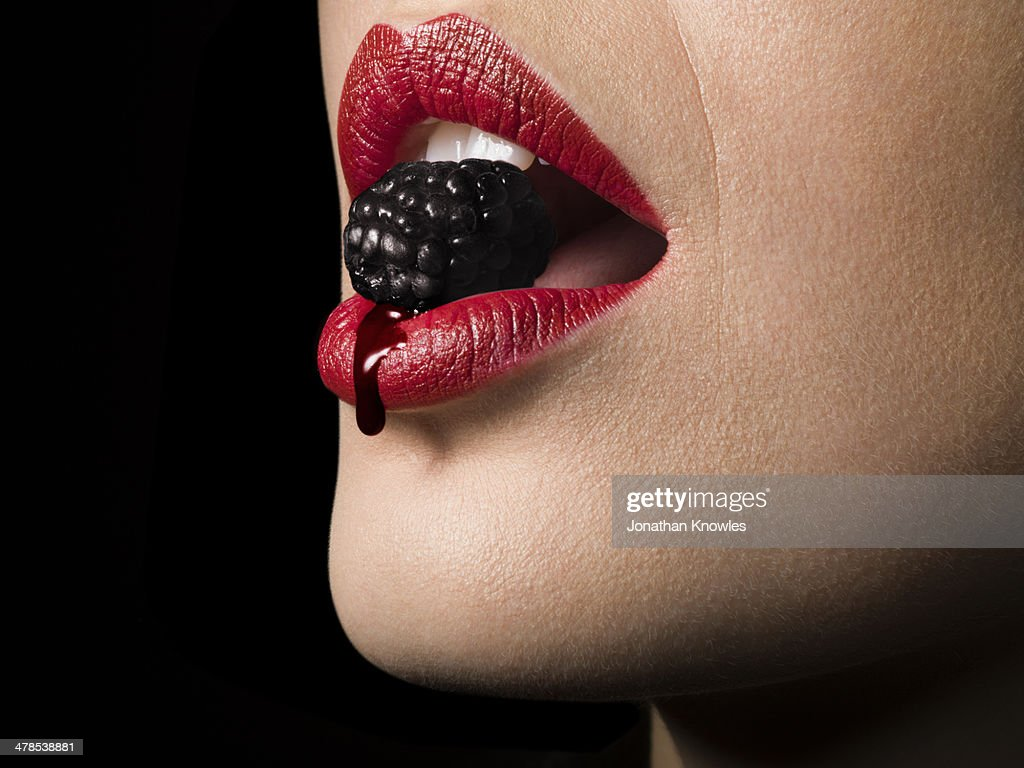 Female with red lipstick biting blackberry, close
