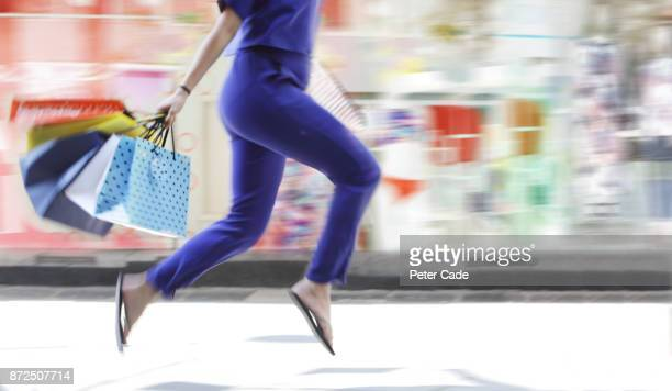 Female with shopping bags passing shop window