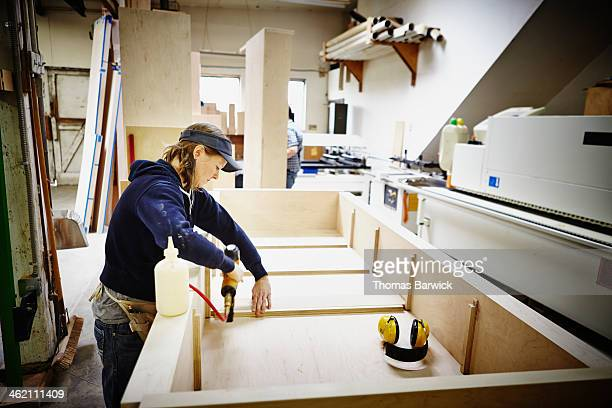 Female woodworker nailing cabinet in woodshop