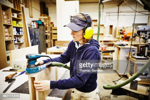 Female woodworker sanding edge of custom cabinet : Stock Photo