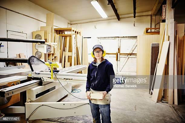 Female woodworker standing in woodshop