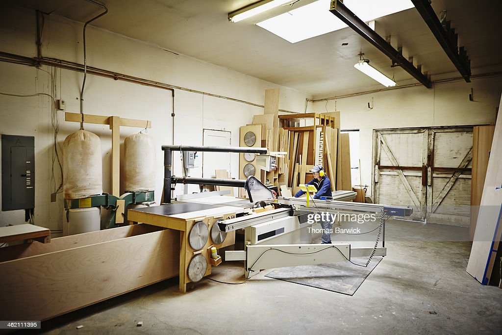 Female woodworker working in woodshop on table saw : Stock Photo