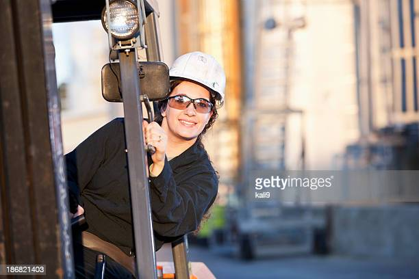 Female worker driving forklift